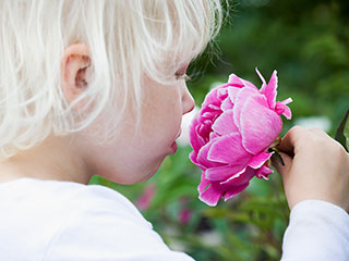 Girl smelling flower.
