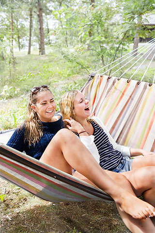 Two laughing friends in hammock.