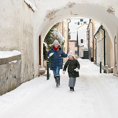 Child and mother in snowy city.