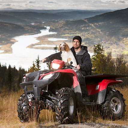 Man with dog on four-wheeler vehicle.