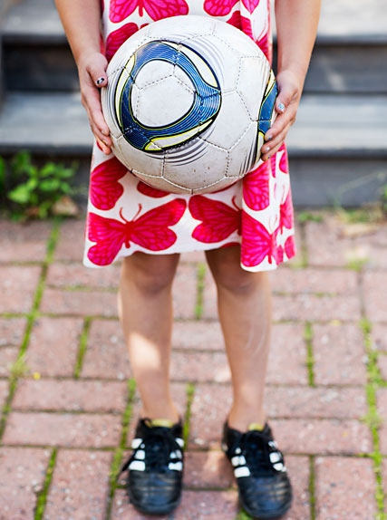 Girl holding a football.